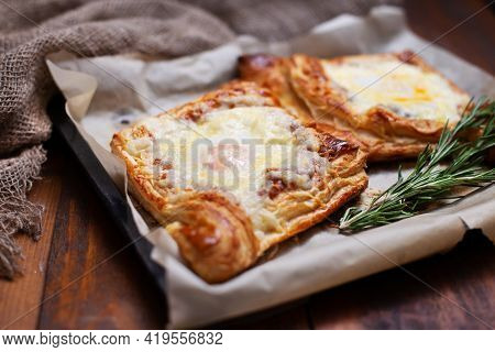 Homemade Georgian Cheese Pastry And Eggs With Rosemary On Baking Paper On Burlap Cloth And Brown Woo