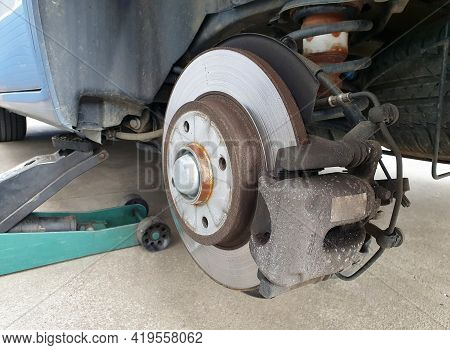 Close Up Of A Car Disc Brake And A Jack During Car Maintenance. Close Up Of Disc Brake Without The W