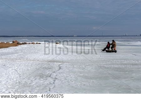 Saint Petersburg, Russia-march 27, 2021: Fishermen In Winter Outfit Are Coming Back From The Winter