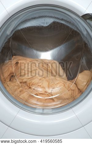 Washing Machine Wrings Out The Laundry Beige Bed Linen, Closeup Window View. Modern Technologies In