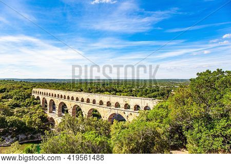 The aqueduct Pont du Gard connects hills covered with dense deciduous forest. The Pont du Gard is the tallest Roman aqueduct. The bright sunny day. Interesting trip to France.