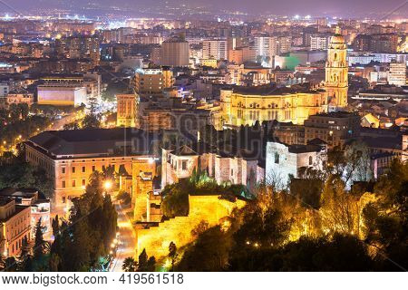 Malaga, Spain view of the Parroquia Santiago Apostol Malaga (Church of Santiago Apostol) along the citycape with the old citadel walls at night.