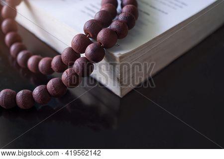 Catholic Rosary Old Bible On Black Wood Background. Christian Catholic Religious Or Religion Ramadan