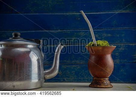 Chimarrão With Ilex Paraguariensis Herb And Aluminum Kettle On Blue Wooden Background. Bitter Mate.