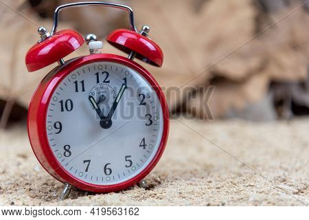 Red Analog Clock And Maple Leaves In The Background