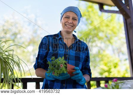 Woman At Home In The Attic Plants Beautiful Flowers In Pots. Takes care of plants. Changes the Earth.