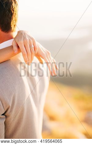 The Bride Hugs The Groom, The Brides Hands With The Wedding Ring On The Grooms Shoulders, Close-up