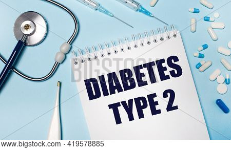 On A Light Gray Background, A Stethoscope, An Electronic Thermometer, Pills, Syringes And A Notebook