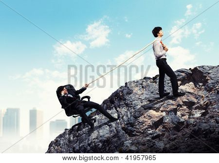Image of two young businessmen pulling rope atop of mountain against city background