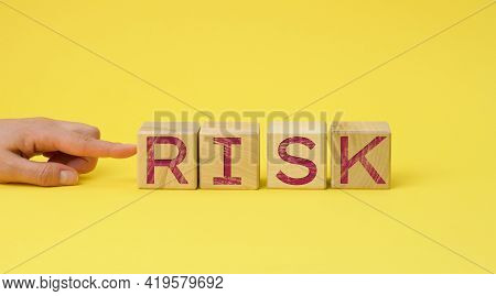 Wooden Cubes With The Inscription Risk On A Yellow Background. Risk Reduction Concept, Reinsurance.