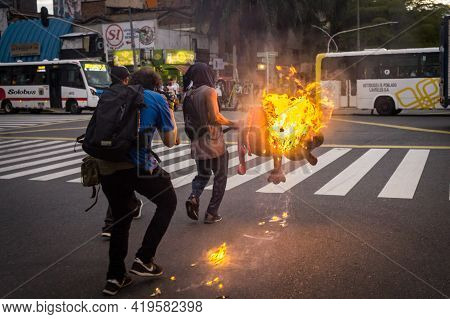 MedellÍn, Colombia - May 03, 2021: A Person Carries A Burning Object To Barricade The Street. Days O