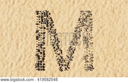 Concept or conceptual stones on beach sand handmade symbol shape, golden sandy background, sign of M. 3d illustration metaphor for education, nature, summer, sunny, seaside and tropical