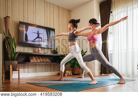 Asian Woman And Little Girl Practicing Yoga From Yoga Online Course Via Smart Tv At Home. Healthy Li