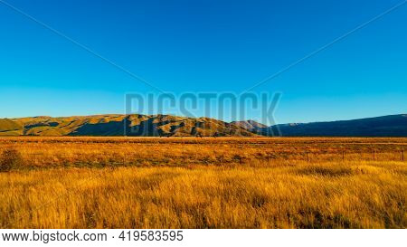 Beautiful Scenic View Of Along Roadside In South Island Of New Zealand Which Have Golden Grass And B