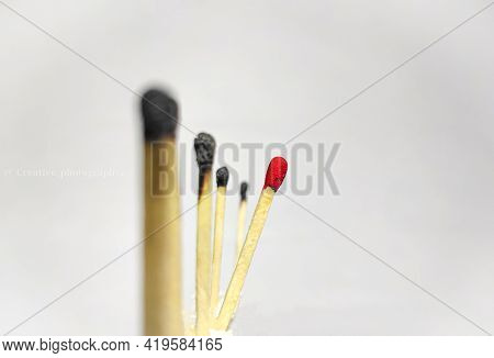 Selective Focus Of Unburnt Matchstick In A Row Of Burnt Matchstick With Copy Space Symbolizing The C