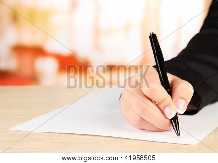 Hand with pen on white paper, on wooden  table on  bright background