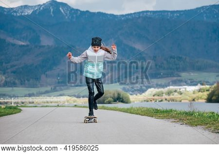 Cute Girl Skateboarding On The Longboard On The Asphalt Road With A Mountain Landscape Background. S