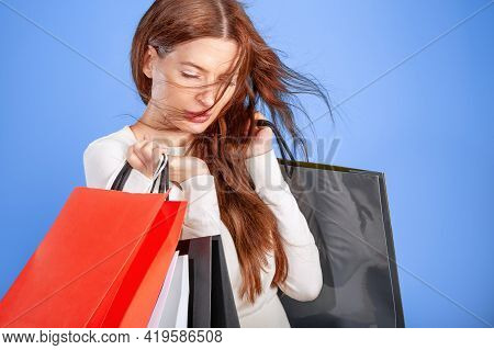 Young Woman With Shopping Bags Against A Blue Background