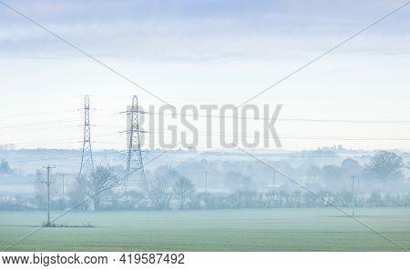 Electricity Pylons In A Uk Landscape On A Misty Morning. Aylesbury Vale, Buckinghamshire, Uk