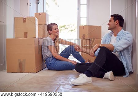 Loving Couple Taking A Break Sitting On Floor Of New Home On Moving Day