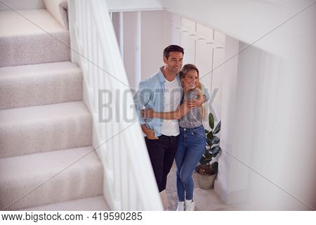 Excited Couple Standing And Hugging In Hallway Of New Home On Moving Day
