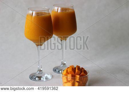 Two Glasses Of Mango Juice With Nicely Sliced Mango Kept Beside. Shot On White Background.
