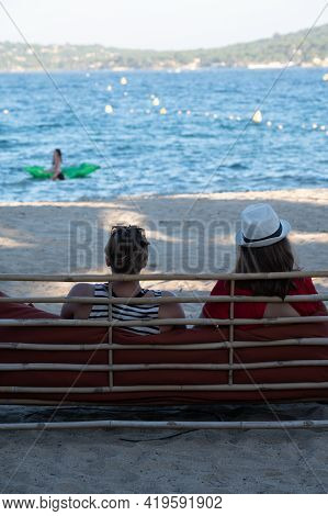 Two Unidentified Woman Sitting In Beach Cafe Lounge En Looking To Blue Water Of Gulf Of Saint-tropez