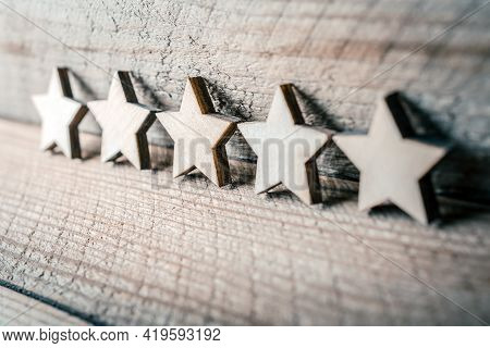 5 Stars Leaning Against A Wooden Wall - Best Quality Concept