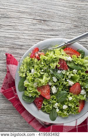 Healthy Green Salad With Strawberry And Fresh Cheese On Wooden Table Background. Healthy Salad Meal.