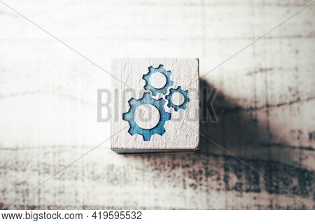 Group Of Gears On A Wooden Block On A Table - Team Success Concept