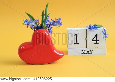 Calendar For May 14: A Bouquet In A Heart-shaped Vase With Blue Flowers And The Numbers 14 On Cubes,
