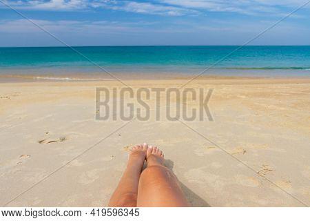 Tanned Female Legs On The Beach By The Sea. Woman Legs Sunbathing On The Beach.