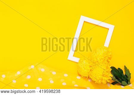 Banner With Flower, Polka Dot Scarf And Blank White Photo Frame On Yellow Background With Copy Space