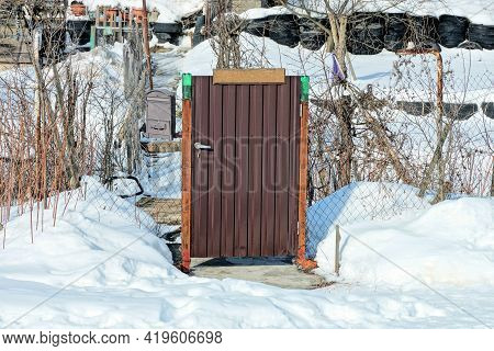 Brown Metal Closed Door And Fence Wall Made Of Gray Iron Mesh In A Snowdrift Of White Snow On A Wint