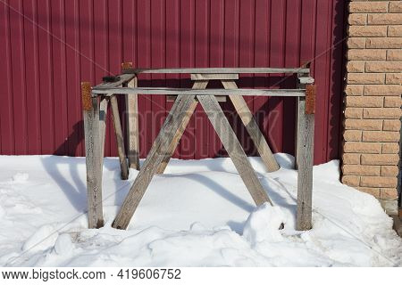 The Frame Of The Box Made Of Gray Wooden Planks Stands In A Snowdrift Of White Snow Near The Red Met
