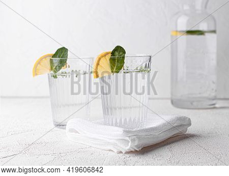 Two Glasses Of Fresh Water, Decorated With Lemon Wedges And Mint Leaves On A White Table. Selective