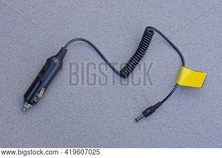 A Black Car Charger With An Electric Wire And A Plug Lies On A Gray Table