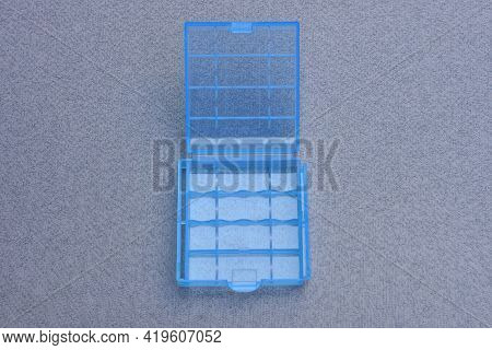 A One Small Open Blue Plastic Box Is On A Gray Table