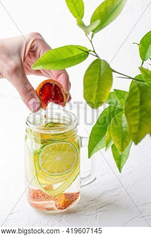A Womans Hand Squeezes A Slice Of Red Orange Into A Glass Mug With Handle With Refreshing Detox Lemo
