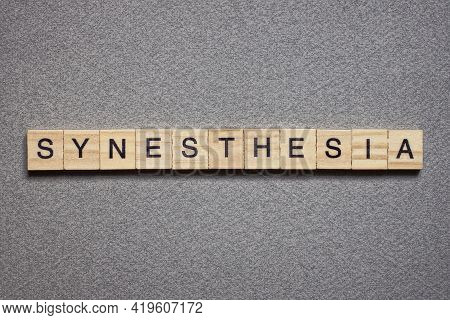 Text The Word Synesthesia From Brown Wooden Small Letters With Black Font On An Gray Table