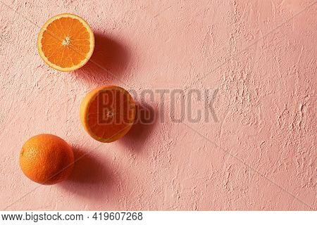 Whole And Cut In Half Ripe Orange On A Orange Concrete Surface. Minimalism. Copy Space