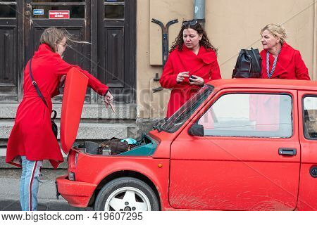 Cesis, Latvia - May 02, 2021: Three Women In Red Clothes At A Red Vintage Car Fiat 126 With An Open