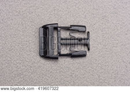 One Black Plastic Carabiner Latch Is On A Gray Table