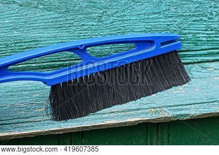 A Large Blue Plastic Brush Sweeps Dust Off The Green Wooden Wall