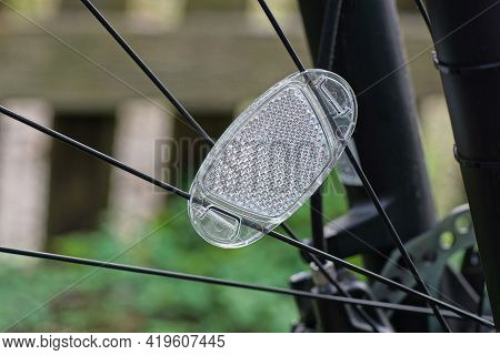 One  White Plastic Reflector On Black Metal Wheel Spokes On The Bicycle