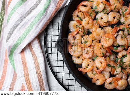 Prawns Fried With Garlic In A Cast Iron Skillet On A White Table With A Striped Linen Napkin. Top Vi