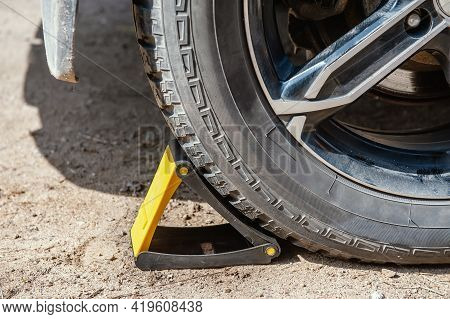 Wheel Chocks For Restricting Movement Under The Wheel Of The Car. Replacing The Wheel On The Road By