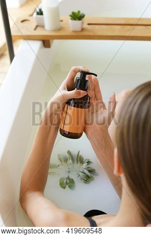 Womans Holding Amber Botles With Spa Cosmetics In Bathroom. Beauty Blogger, Salon Therapy, Minimalis