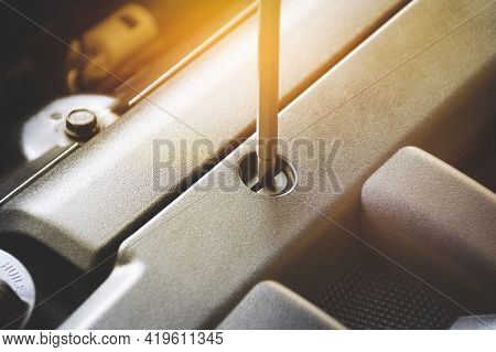 Screwdriver Is Unscrewing To Car Fastener Clips Of The Car Engine Cover
