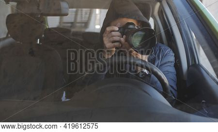 A Man In Black Glasses And A Hoodie At The Wheel Of A Car Is Secretly Shooting On A Long-focus Lens.